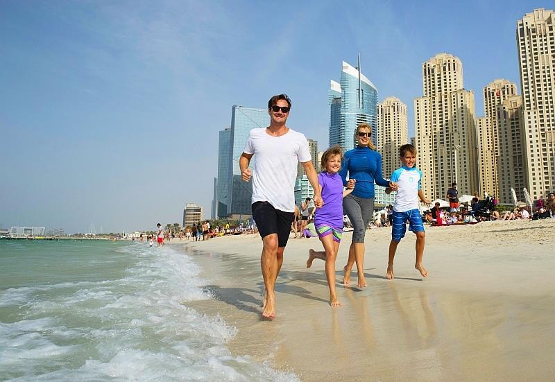 Junge Familie läuft am Jumeirah Beach in Dubai