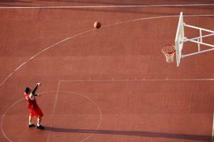 Basketballplatz mit Korb und einem Spieler