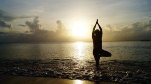Frau macht bei Sonnenuntergang Yoga am Strand