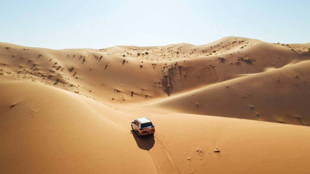 Allradfahrzeug fährt offroad durch die Wüste in Abu Dhabi
